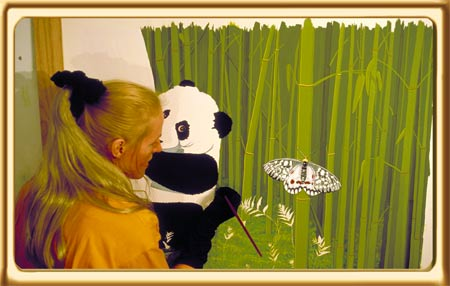 With her long blonde hair tied back, Allex Michael paints a panda in bamboo with a butterfly.