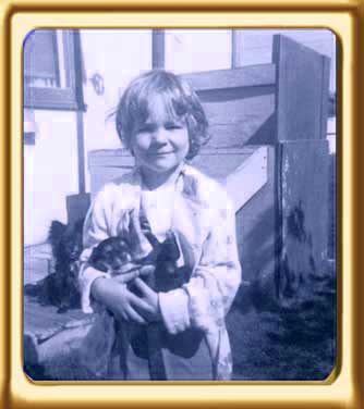 Allex Michael as a child holding a puppy in front of a run down house.